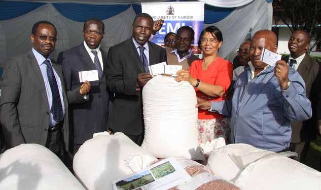 Prof. Agnes Mwang ombe, Principal, CAVS hands over bean seed varieties to representatives of Kenya Seed Company.