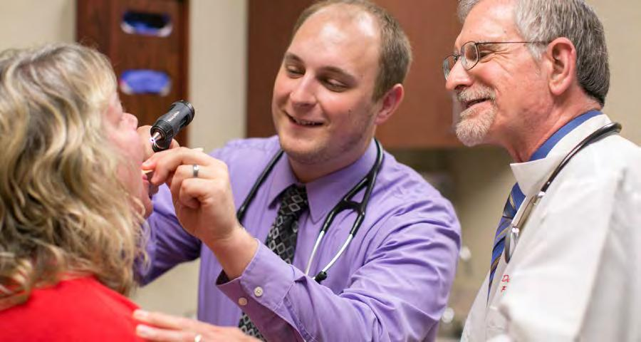 2. EDUCATION Belleville resident Lucas Kuehn, MD (center) examines a patient as David Deci, MD, oversees.