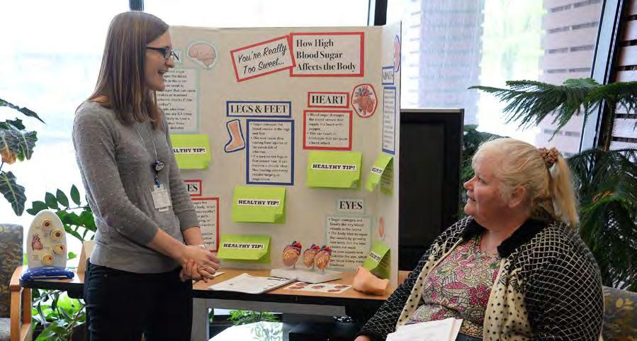 4. COMMUNITY HEALTH Alison Hotujec, MD (left), talks with a patient at a diabetes health fair she led at the UW Health Odana Atrium Clinic.